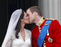 <p>Britain's Prince William and his wife Catherine, Duchess of Cambridge, kiss as they stand on the balcony at Buckingham Palace with other members of the Royal Family, after their wedding in Westminster Abbey, in central London April 29, 2011. REUTERS/Darren Staples</p>