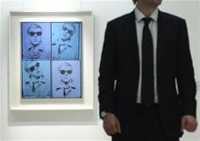 """<p>A Christie's employee poses for a photograph with artist Andy Warhol's """"Self-Portrait"""" at Christie's auction house in London April 15, 2011. REUTERS/Luke MacGregor</p>"""