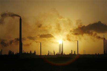 The sunset is seen behind Isla refinery in Willemstad on the island of Curacao in this picture taken June 16, 2008. REUTERS/Jorge Silva