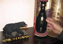 <p>A bottle of bear bile liquor is pictured next to a black bear sculpture in a new Guizhentang shop in Beijing February 17, 2011. REUTERS/Jason Lee</p>