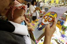 <p>A baby looks at the cartoon character Pororo at a book store in Seoul May 16, 2011. REUTERS/Truth Leem</p>
