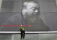 <p>A worker attaches a banner showing Chinese artist Ai Weiwei, to the Lisson Gallery in London May 11, 2011. REUTERS/Andrew Winning</p>