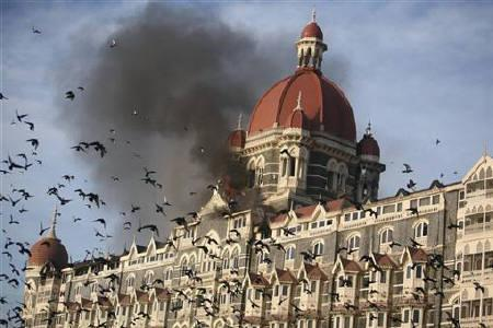 Pigeons fly near the burning Taj Mahal hotel during the Mumbai terror attacks in Mumbai November 27, 2008. U.S. prosecutors on Monday outlined an elaborate plot that allegedly preceded the 2008 attack on Mumbai, saying Chicago businessman Tahawwur Rana helped make it possible for militants to scout their targets. REUTERS/Punit Paranjpe/Files