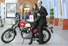"""<p>Thriller writer Jeffery Deaver (R) poses for photographers with model Chesca Miles on a BSA Spitfire motorbike to launch the new James Bond book """"Carte Blanche"""" at St Pancras station in London May 25, 2011. REUTERS/Paul Hackett</p>"""
