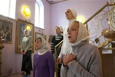 <p>Followers of Svetlana Frolova pray during a service at her sanctuary at Bolshaya Yelena, a village near central Russia's city of Nizhny Novgorod May 15, 2011. God spoke to Frolova and revealed that Russian leader Vladimir Putin is the reincarnation of St.Paul the Apostle, or so she says. The cult lead by Frolova, a former railway manager who was jailed for fraud in 1996, is the most extreme illustration of a growing personality cult which venerates Putin as paramount leader ahead of the 2012 presidential election. Picture taken May 15. REUTERS/Natalia Plankina</p>