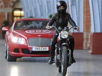 """<p>Model Chesca Miles arrives on a BSA Spitfire motorbike to launch the new James Bond book """"Carte Blanche"""" at St Pancras station in London, May 25, 2011. REUTERS/Paul Hackett</p>"""
