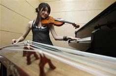 "<p>Taiwanese musician Shara Lin Yi-Hsin, 25, poses for a photograph during an interview with Reuters in Taipei May 25, 2011. A video of Lin, which showed her performing Taiwanese singer Jolin Tsai's ""Dancing Diva"" by simultaneously playing the piano, violin, and zither, has attracted wide internet attention. REUTERS/Pichi Chuang</p>"