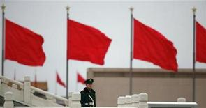 <p>A paramilitary policeman stands guard near red flags on Tiananmen Square during the closing ceremony of the National People's Congress (NPC) inside the adjacent Great Hall of the People in Beijing March 14, 2011. REUTERS/Petar Kujundzic</p>