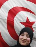 <p>A Tunisian student from El Kef smiles next to a Tunisian flag in Tunis February 9, 2011, during a demonstration against two civilians who were shot and killed last week in El Kef. REUTERS/Louafi Larbi</p>