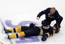 """<p>A trainer kneels over the Boston Bruins' Nathan Horton after Horton was hit by the Vancouver Canucks' Aaron Rome (not pictured) during the first period in Game 3 of the Stanley Cup hockey playoff in Boston, Massachusetts, June 6, 2011. The Boston Bruins announced June 7 that Horton will miss the remainder of the playoffs due to a """"severe concussion."""" REUTERS/Brian Snyder REUTERS/Brian Snyder</p>"""