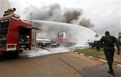 <p>Emergency services work at the scene of an explosion at a police station after a suspected suicide bomber was killed and many vehicles were destroyed in Abuja June 16, 2011. REUTERS/Afolabi Sotunde</p>