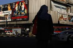 <p>A woman stands in front of a street with posters of Indonesian films in Jakarta June 21, 2011. REUTERS/Beawiharta</p>