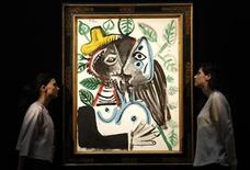 "<p>Sotheby's employees pose with artist Pablo Picasso's artwork ""Couple, le baiser"" at Sotheby's Auction House in London June 17, 2011. REUTERS/Luke MacGregor</p>"