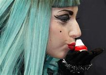 <p>Lady Gaga kisses a Okiagari-koboshi doll which symbolizes resilience and perseverance, at a news conference in Tokyo June 23, 2011. REUTERS/Issei Kato</p>