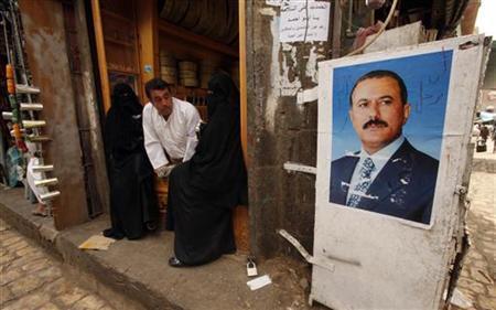 People sit near a picture of Yemen's President Ali Abdullah Saleh in the old city of Sanaa June 20, 2011. REUTERS/Suhaib Salem