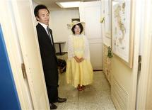 "<p>Tomoharu (L) and Miki Saito wait outside the venue of their ""divorce ceremony"", as their son plays with a toy, in Tokyo July 3, 2011, a day before they file for divorce. REUTERS/Yuriko Nakao</p>"