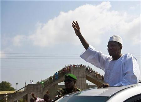 Guinea president-elect Alpha Conde waves to his supporters after leaving Conakry's Grand Mosque December 3, 2010. REUTERS/Joseph Penney