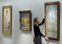 "<p>A Christie's employee poses with artist Claude Monet's ""Les Peupliers"" at Christie's auction house in London April 15, 2011. REUTERS/Luke MacGregor</p>"