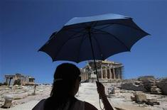 <p>A tourist walks in front of the Parthenon temple at the Acropolis hill in Athens, July 10, 2011. Picture taken July 10, 2011. REUTERS/John Kolesidis</p>
