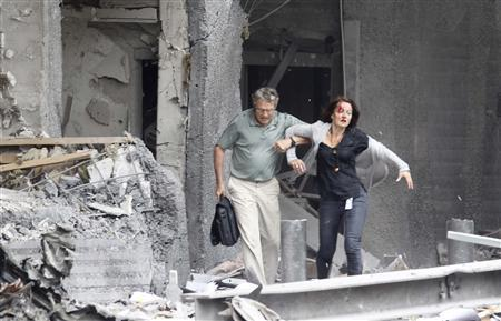 An injured woman is helped by a man at the scene of a powerful explosion that rocked central Oslo July 22, 2011. REUTERS/Morten Holm/Scanpix