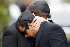 <p>Mourners embrace as they leave the funeral service for Amy Winehouse at a cemetery in north London July 26, 2011. REUTERS/Stefan Wermuth</p>