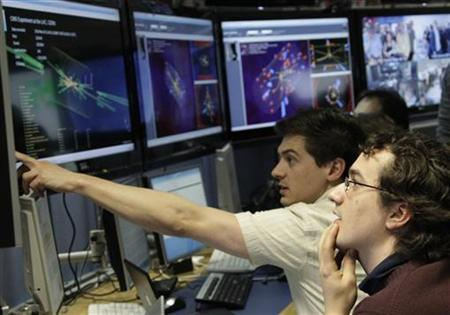 Scientists look at pictures of the first successful collisions at full power at the control room of the Large Hadron Collider (LHC) at the European Organisation for Nuclear Research (CERN) in Meyrin, near Geneva, March 30, 2010. REUTERS/Denis Balibouse