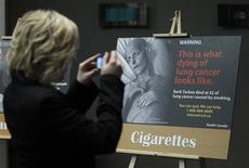 <p>A woman takes a photo of a display showing new warning labels for cigarette packages following a news conference in Ottawa December 30, 2010. REUTERS/Chris Wattie</p>
