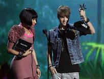 <p>Singer Justin Bieber accepts the best male hip hop artist for Kanye West from co-presenter Nicki Minaj at the 2011 BET Awards in Los Angeles June 26, 2011. REUTERS/Mario Anzuoni</p>