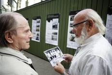 <p>Visitors Zigmas Vitkauskas (L) and Edvardas Brokas observe a picture of the Soviet gulag labour camp basketball team during an exhibition in Vilnius August 24, 2011. REUTERS/Ints Kalnins</p>