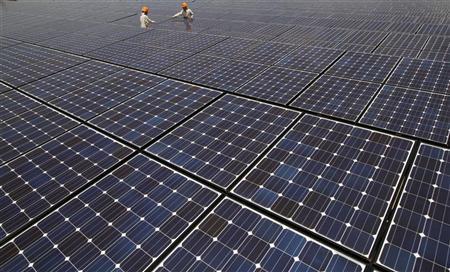Workers check solar panels at a solar power field in Kawasaki, near Tokyo July 6, 2011. REUTERS/Toru Hanai (JAPAN - Tags: BUSINESS ENERGY ENVIRONMENT)