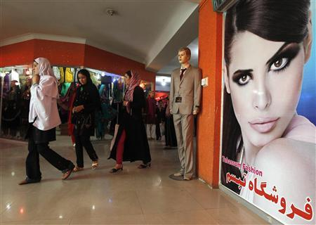 Women walk past a poster at a shopping mall in Kabul August 25, 2011. REUTERS/Omar Sobhani
