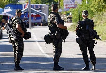 Slovenia's KFOR soldiers look at the road blockade in the village of Rudare near Mitrovica August 8, 2011. REUTERS/Ivan Milutinovic