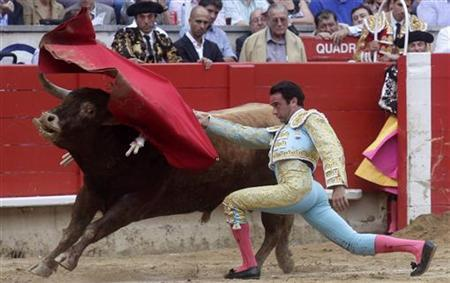 Spanish bullfighter Enrique Ponce performs a pass to a bull during a bullfight at Monumental bullring in Barcelona July 17, 2011. REUTERS/Albert Gea