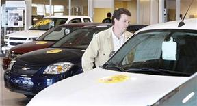 <p>A customer looks at new cars at a General Motors dealership in Quebec City, June 1, 2009. REUTERS/Mathieu Belanger</p>
