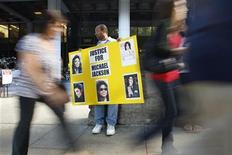 <p>Activist Najee Ali holds a poster with photos of late pop star Michael Jackson outside the Criminal Courts building in Los Angeles, California as jury selection begins in the involuntary manslaughter trial of Jackson's doctor Conrad Murray September 8, 2011. REUTERS/David McNew</p>