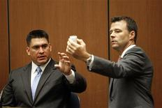 <p>Deputy District Attorney David Walgren (R) holds a bottle of propofol introduced as evidence as he questions Alberto Alvarez (L), one of Michael Jackson's security guards, during Dr. Conrad Murray's trial in the death of pop star Michael Jackson in Los Angeles September 29, 2011. REUTERS/Al Seib/Pool</p>