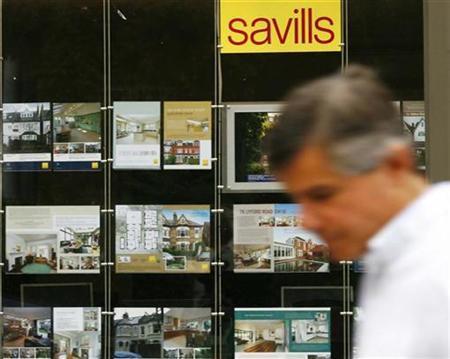 A pedestrian passes a branch of estate agent, Savills, in London August 28, 2008. REUTERS/Luke MacGregor