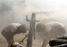 """<p>U.S. soldiers from Alpha Co, 2nd Battalion 35th Infantry, Task Force """"Cacti"""", fire a 120mm mortar round at Taliban positions from Combat Outpost Penich in Shalay Valley, in Kunar province, near the Afghanistan-Pakistan border October 4, 2011. REUTERS/Erik De Castro</p>"""