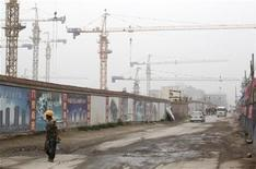 <p>A worker walks past a residential construction site in Beijing June 23, 2011. REUTERS/Soo Hoo Zheyang</p>