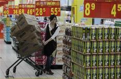 <p>An employee pulls a trolley loaded with boxes of products at a supermarket in Wuhan, Hubei province, October 13, 2011. REUTERS/Stringer</p>