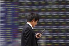 <p>A man walks past a stock quotation board outside a brokerage in Tokyo October 24, 2011. REUTERS/Toru Hanai</p>