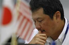 <p>A foreign exchange broker rests his thumb on his lips as he is pictured near Japanese and American flags at a trading room in Tokyo October 26, 2011. REUTERS/Yuriko Nakao</p>