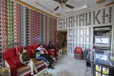 """<p>Vishal Singh (2nd R), 38, sits in his living room with his 35-year-old wife Ruchi Singh (R), 15-year-old daughter Simran (L) and five-year-old son Aryan in Lucknow October 24, 2011. Singh is a fan of the Bollywood actor Shah Rukh Khan and has more than 22,000 pictures of the star in his possession. Singh's house, which he calls """"Shahrukh palace,"""" and even his workplace, are covered with posters featuring the actor. Singh even changed his name to Vishahrukh Khan as a display of his love for the actor. REUTERS/Pawan Kumar</p>"""