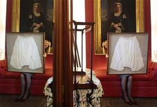 <p>Kate Bain from Lyon and Turnbull auctioneers poses for photographers with a framed pair of silk bloomers undergarments that once belonged to Queen Victoria, during a photocall for the auction of the Forbes Collection in Edinburgh, Scotland October 27, 2011. REUTERS/David Moir</p>