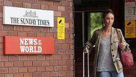 <p>Foto de archivo de una mujer a las afueras de las oficinas de News International en Londres, jul 6 2011. El escándalo de escuchas telefónicas que envuelve a News Corp, del magnate Rupert Murdoch, amenazaba con propagarse el viernes tras el arresto de un periodista del diario The Sun por acusaciones de soborno a policías, de acuerdo a fuentes de la compañía. REUTERS/Olivia Harris</p>