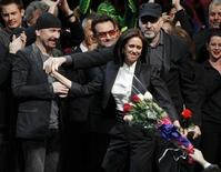 """<p>Director Julie Taymor (C) is handed a bouquet of flowers as she takes the stage along with The Edge (L) and Bono of U2 and director Philip William McKinley (R) during the curtain call for the Broadway opening of """"Spider-Man: Turn Off The Dark"""" in New York City June 14, 2011. REUTERS/Jessica Rinaldi</p>"""