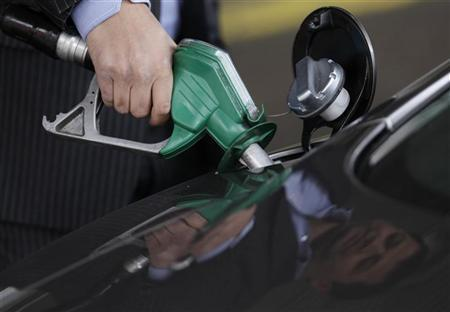 A customer fills his Aston Martin DB9 car at a petrol station, in south London, March 2, 2011. REUTERS/Andrew Winning