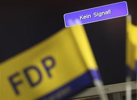 A flag of the liberal Free Democratic party FDP is pictured in front of a monitor during an election party in the state elections of North Rhine-Westphalia NRW, in Duesseldorf May 9, 2010. REUTERS/Ralph Orlowski