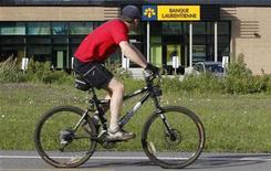 <p>A man cycles past by a Laurentian Bank branch in Quebec City June 9, 2010. REUTERS/Mathieu Belanger</p>