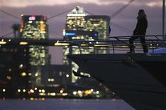 <p>A woman poses on-board a yacht with Canary Wharf behind at the London Boat Show at the ExCeL centre in London, January 6, 20011. REUTERS/Luke MacGregor</p>